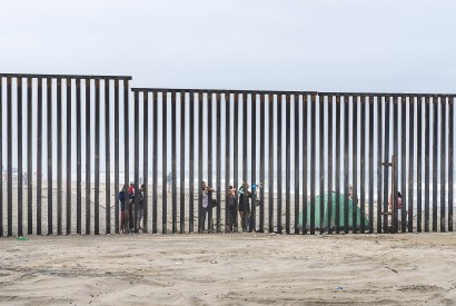 Mexican citizens holding up crosses at the border wall. Bread for the World photo