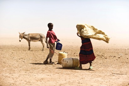 A Kenyan woman and boy struggle with the dusty wind looking for water. This is what climate change looks like in Kenya and other parts of sub-Saharan Africa. Jervis Sundays/Kenya Red Cross Society.