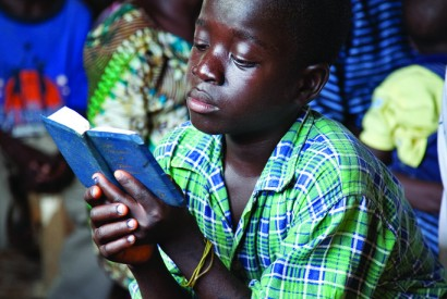 A boy reads his Bible at an Assemblies of God service in Saclepea, Liberia. Laura Elizabeth Pohl/Bread for the World.