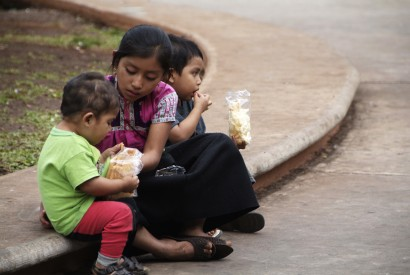 Three kids sit on a curb in Mexico while eating a snack. Margie Nea for Bread for the World.