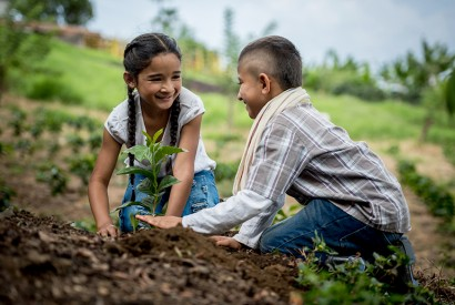 Children planting a tree on their farm. iStock