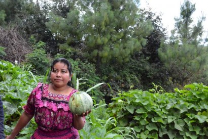 Mother holding crop in her home garden. Photo courtesy of USAID.