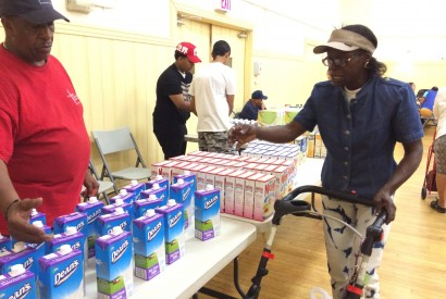 Susan La-Rose selects milk for her daughters at the food pantry at Catholic Charities' Lt. Joseph P. Kennedy Jr. Community Center in Harlem as volunteer Aubrey Woods looks on.