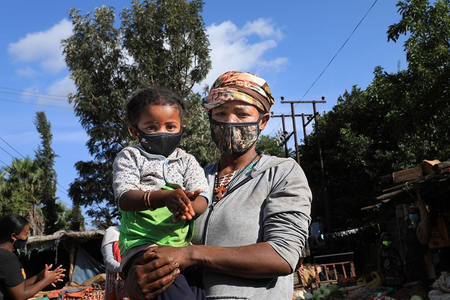 Four-year-old Beamlak rubs her hands with sanitizer. Her mother, Aster Bizago, makes a living by selling vegetables. Aster is worried about both her child's safety and the decline in she is making amid the increasing spread of the coronavirus in Addis Aba
