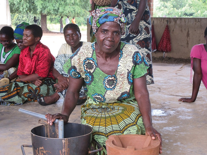 The clay stove this Malawian woman is pictured with has reduced the amount of time she spends collecting firewood by hundreds of hours per year. Alongside the stove she shows off the mold used to make it. Photo by Todd Post / Bread for the World