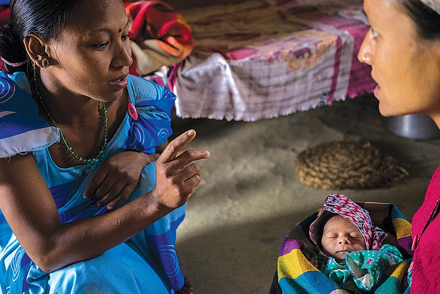A community health worker in Nepal performs a routine check-up on mother and baby to make sure both are healthy. Photo: USAID
