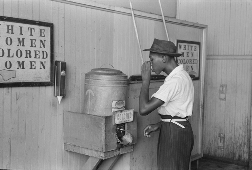 "African-American drinking at a ""Colored"" water cooler in streetcar terminal, Oklahoma City, Oklahoma in July 1939. Russell Lee"