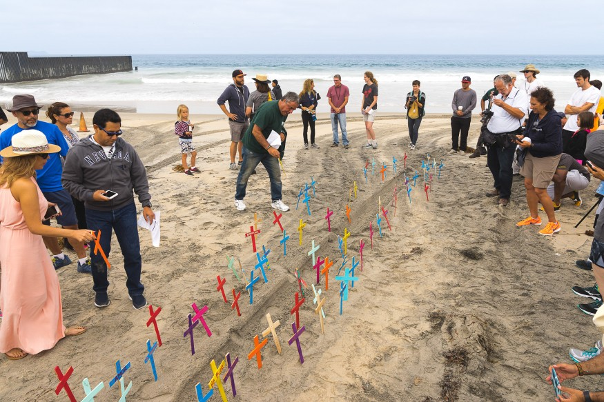 Enrique Morones placing crosses in the sand with participants. Each cross represents a deceased individual who lost their life crossing the border. Johnny Lim for Bread for the World.