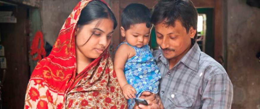 After the birth of her 8-month-old daughter Debi, Asha Rani and husband Bikash Sarker subscribed to the Aponjon mobile health messaging service to receive information about keeping their new baby and the entire family healthy. Tanvir Murad Topu for USAID.