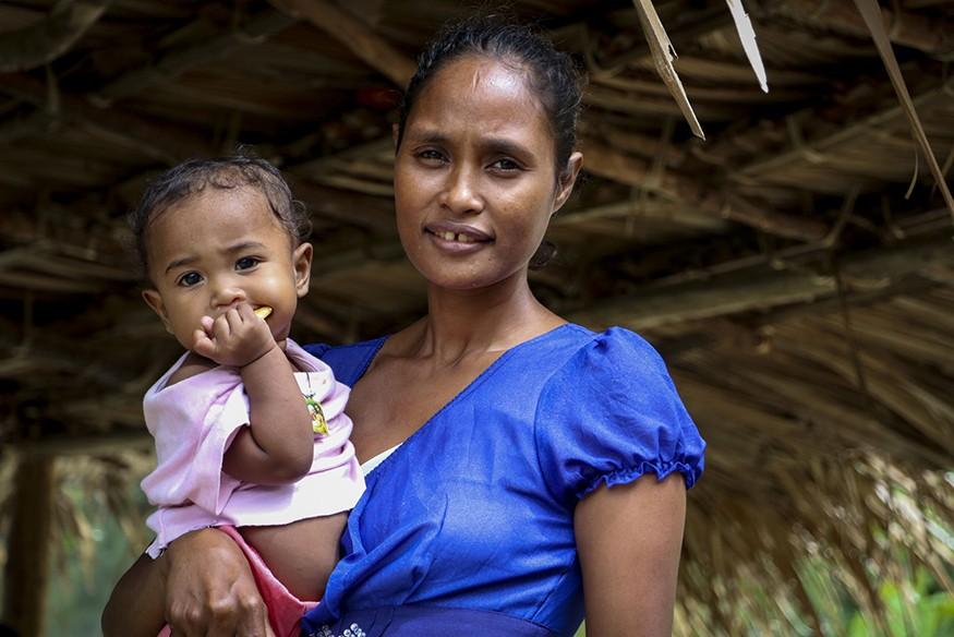 Eliza da Costa Martins, 34, pictured in Libagua village, Timor Leste, with her daughter, Cidalria da Costa Magno, 1. Anna Djahova/CRS
