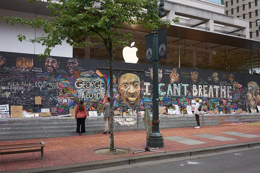 Portland, OR, USA - Jun 12, 2020: Passers-by stop and take a look at the boarded-up Apple Store in downtown Portland's Pioneer Place, which has become unofficial canvases for peaceful protest. Artists have also joined to promote peace. iStock