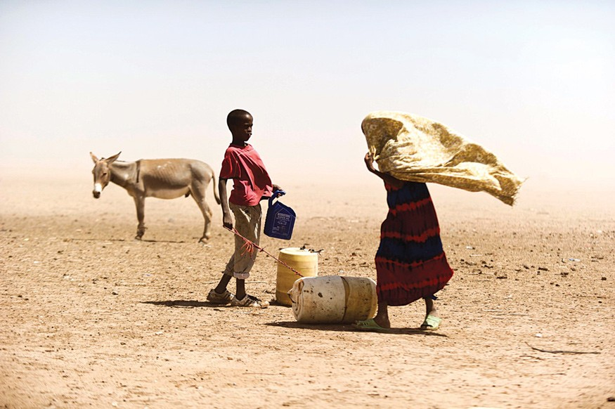 A Kenyan woman and boy struggle with the dusty wind looking for water. This is what climate change looks like in Kenya and other parts of sub-Saharan Africa. Photo by Jervis Sundays / Kenya Red Cross Society