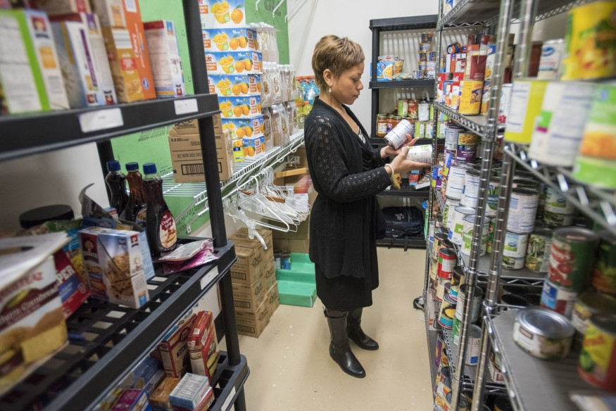 Mental health counselor Candace Layne stocks shelves in the campus food pantry at Mountwest Community and Technical College in Huntington, W.V. Lacey Johnson for Bread for the World