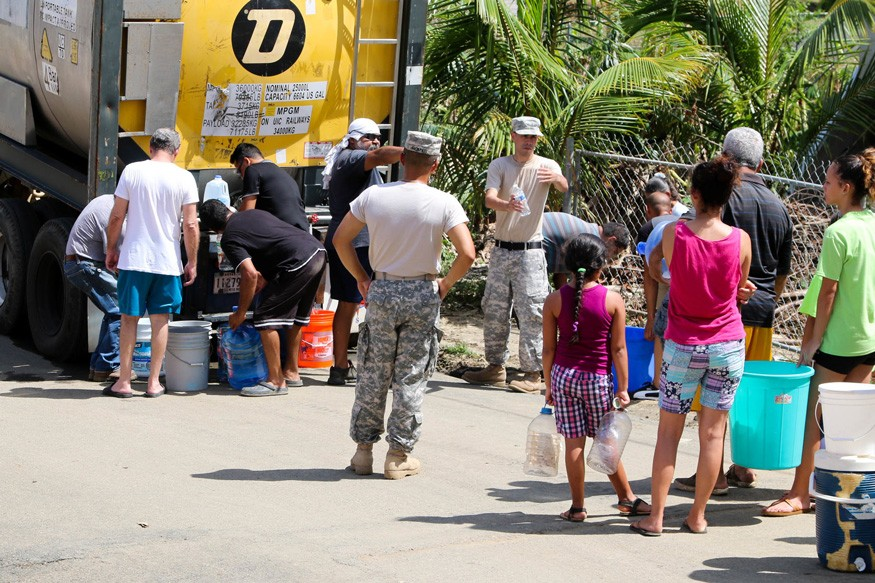 Residents in Toa Baja, Puerto Rico waiting in line to get water brought by the Puerto Rico National Guard. Alexis Velez/Wikimedia Commons.