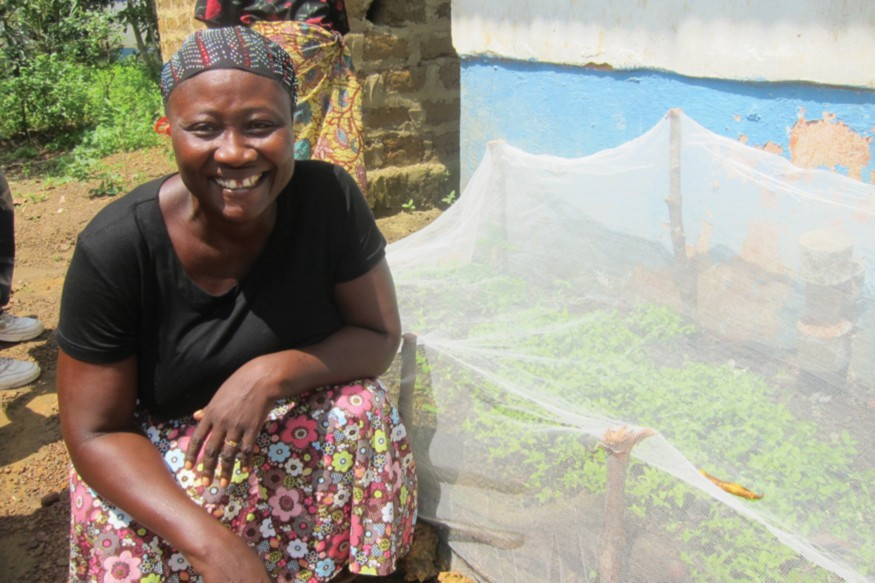 Respect shows off her newly grown peppers planted with seeds provided through USAID. Photo: Mette Karlsen/USAID
