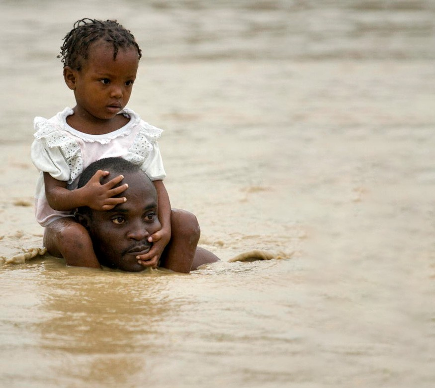 "A father carries his daughter on the shoulders as residents flee rising waters in search of shelter, after heavy rains caused by tropical storm 'Noel"" flooded their homes in Cité Soleil, Haiti. UN Photo / Logan Abassi"