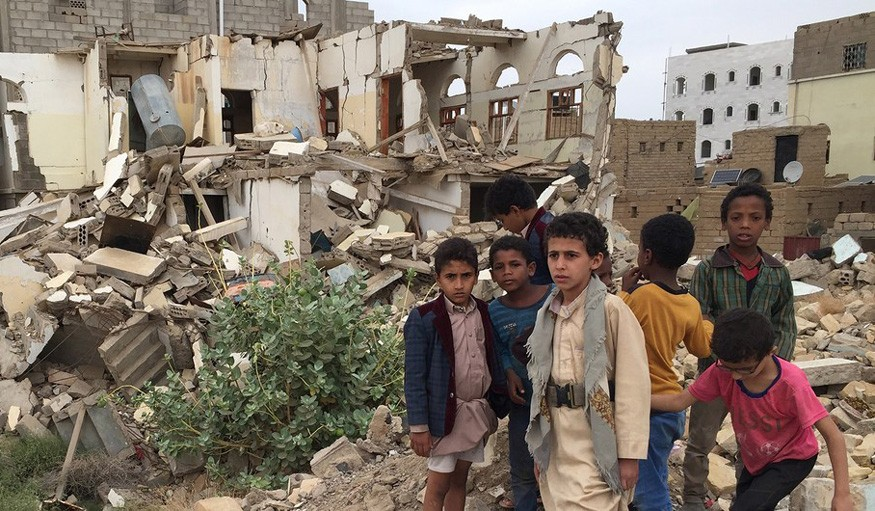 Young boys standing in front of damaged buildings in Saada, Yemen, where bombing has left many neighborhoods in the city are strewn with wreckage and debris following ground fighting between armed groups. Photo: WFP / Jonathan Dumont